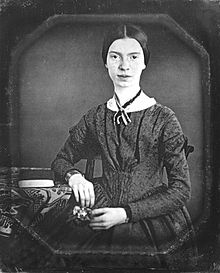 A woman, Emily Dickinson, in a black and white photograph, is sitting next to a desk.
